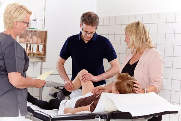 Dr. Sebastian Skawran untersucht das Knie von einem Jungen.