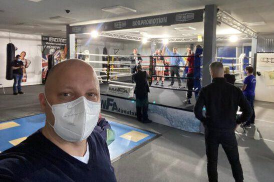 Dr. Timm Schmidt-Mertens vor dem Ring, während Elina Tissen um die Weltmeisterschaft boxt